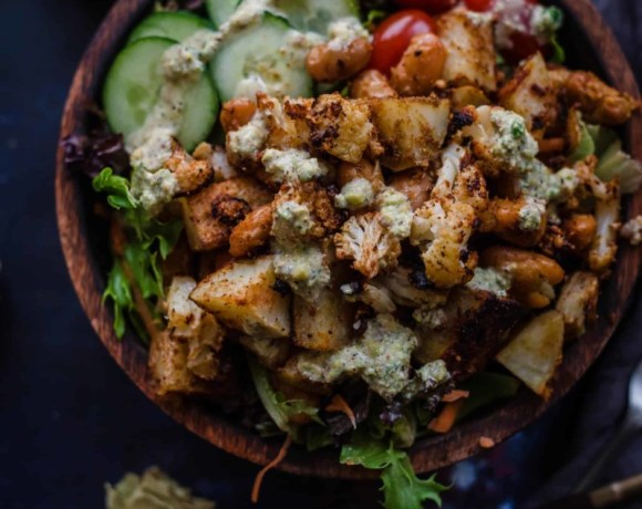 Roast cauliflower salad in a bowl with dressing to side