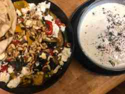Roast veg, feta, pine nuts and pitta bread in plate with yoghurt dip