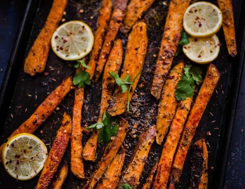 Oven baked sweet potato fries in a tray with lemons
