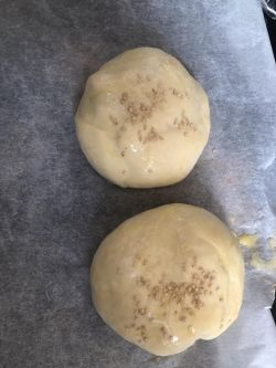 2 buns with egg wash and sesame seeds on lined tray