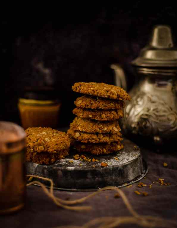 Anzac biscuits in a pile with kettle behind