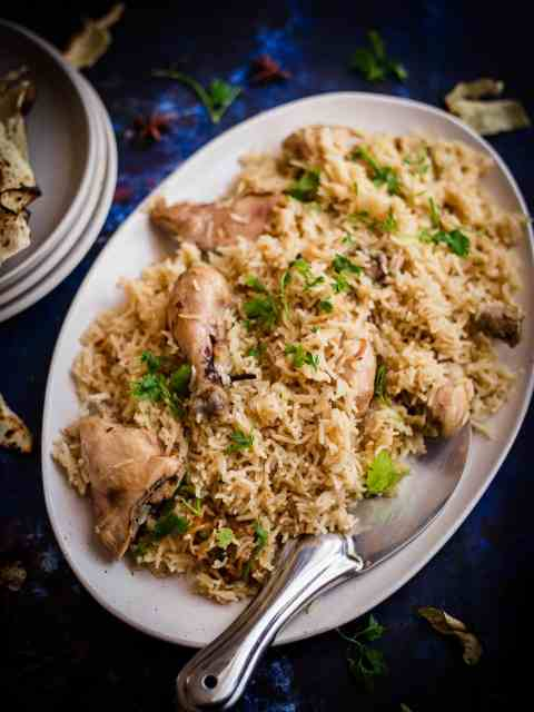 Chicken Pulao in dish with plates and papad to side