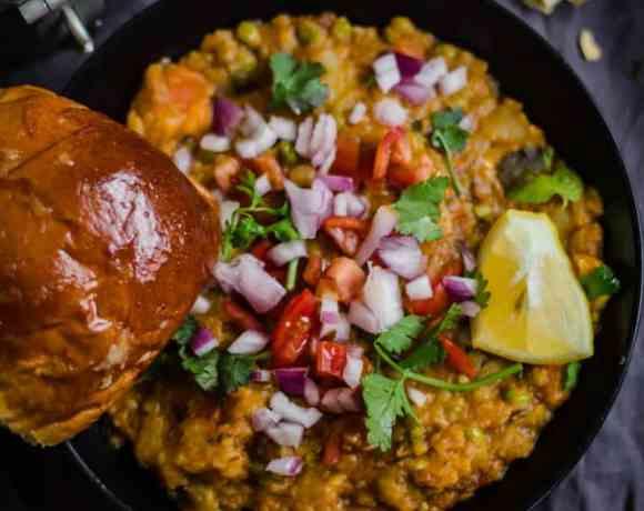Pav Bhaji in dark plate with flowers around it