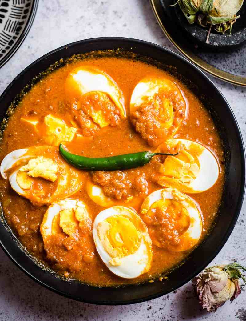 Egg Curry in bowl with plates to side