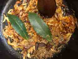 Whole garam Masala and cumin seeds in pot with onions