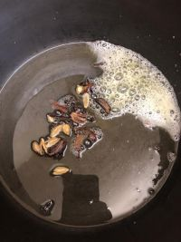 Whole spices added to pot with ghee and oil