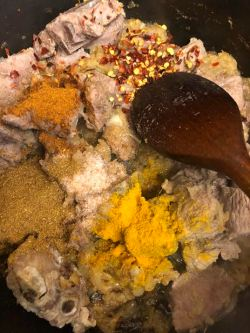 Spices added to pot on top of par cooked meat