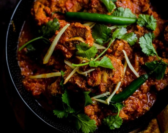 Lamb Karahi in black bowl with Green Chillies and sliced ginger on top