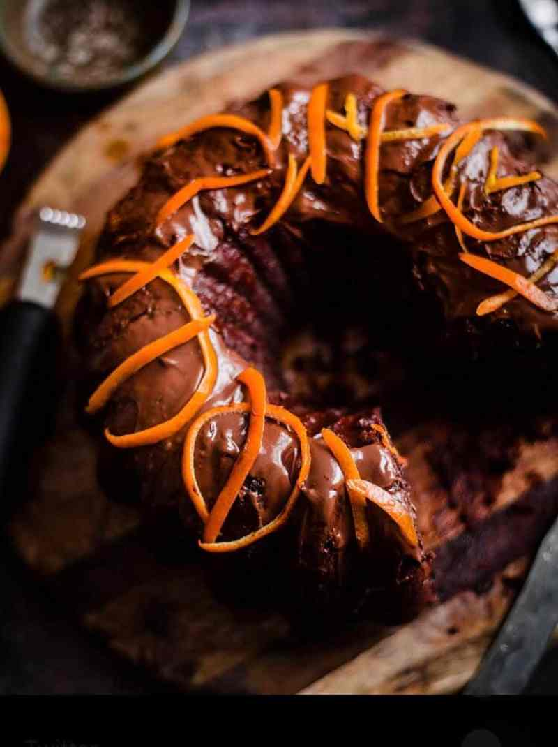 Chocolate Orange Cake on a wooden board with orange peel on top