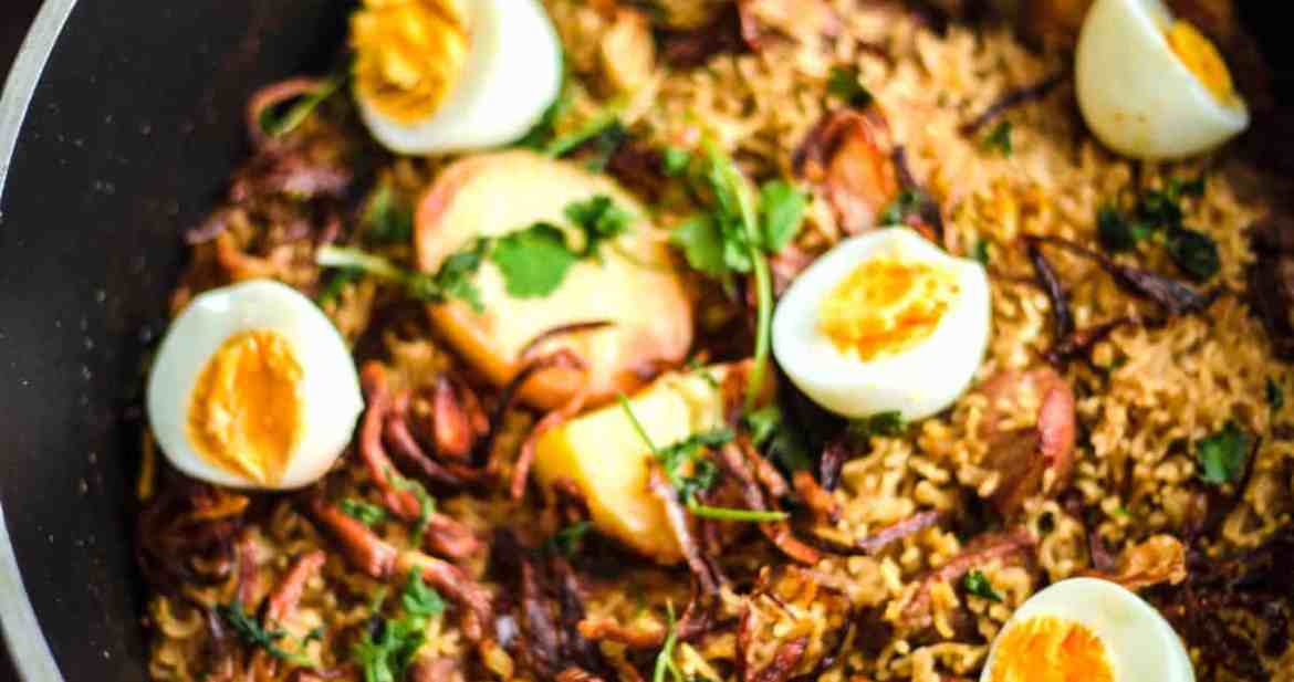 Pakistani Chicken Biryani Recipe in a pot with Eggs on top and salad to back