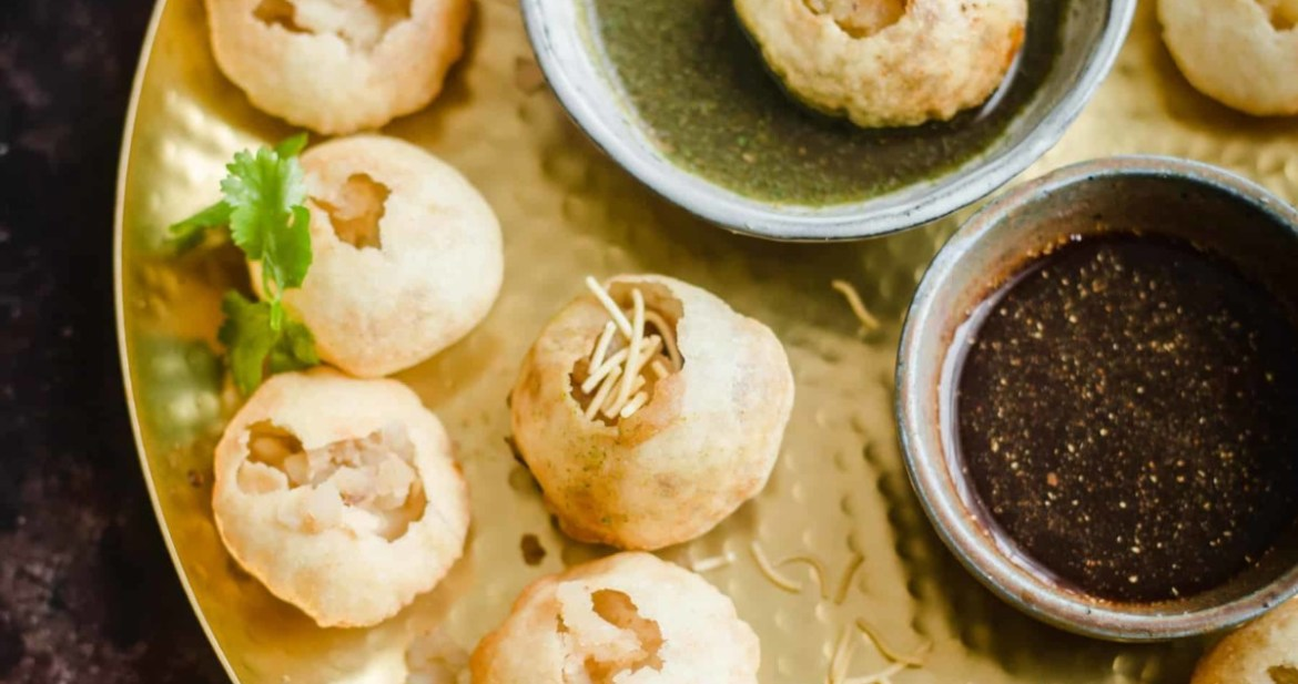 Puris on a platter with chutneys in the middle