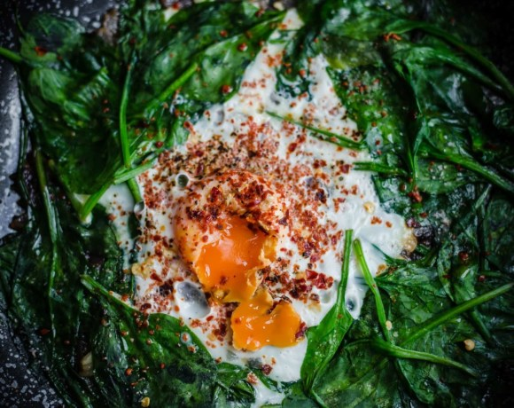 Spinach and Eggs in a pan with runny centre