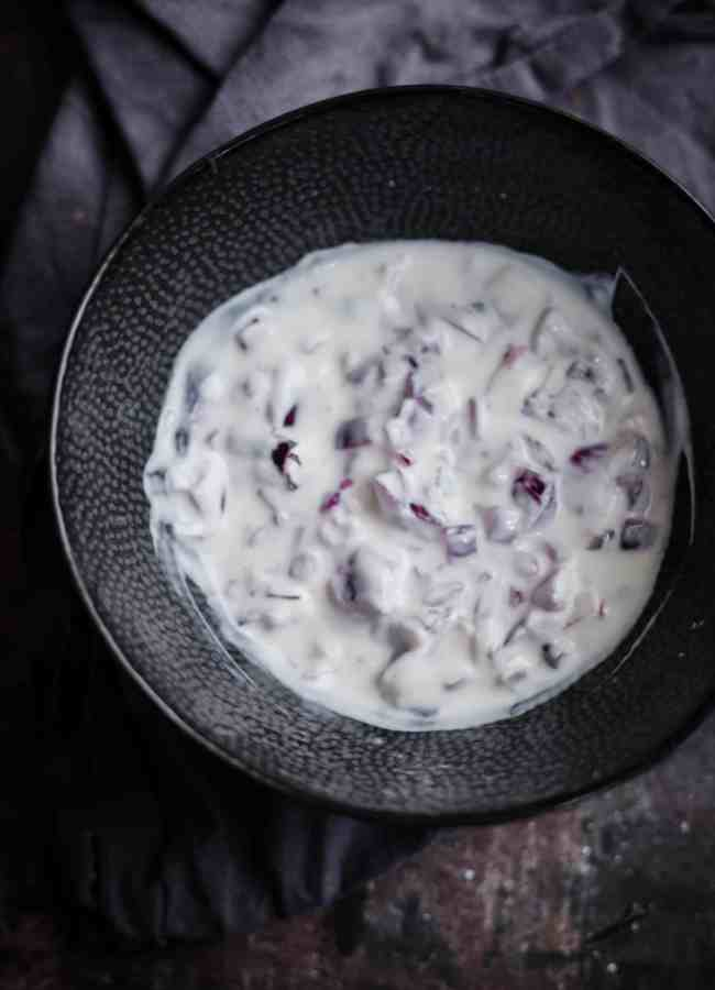 Onion raita in a bowl with a towel to back
