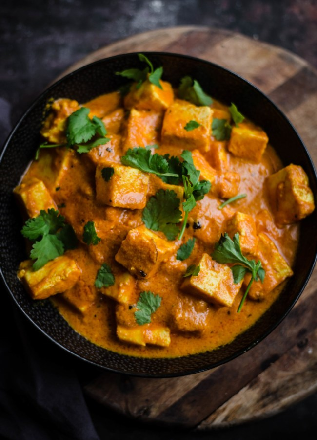 Paneer Makhani in a black bowl on wooden board