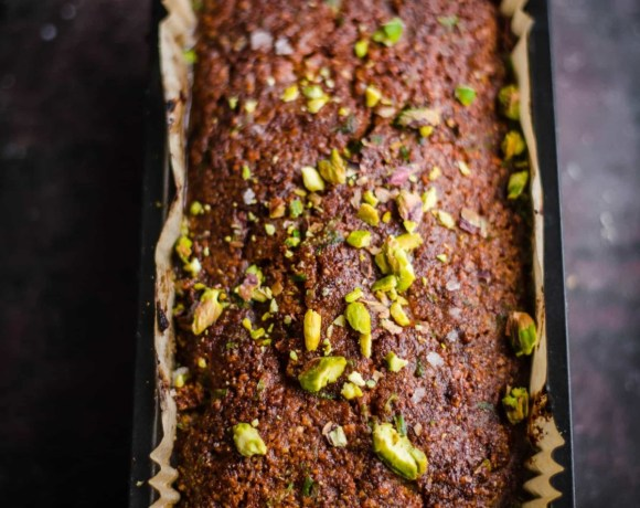 Pistachio Loaf Cake in a loaf tin with pistachios on top