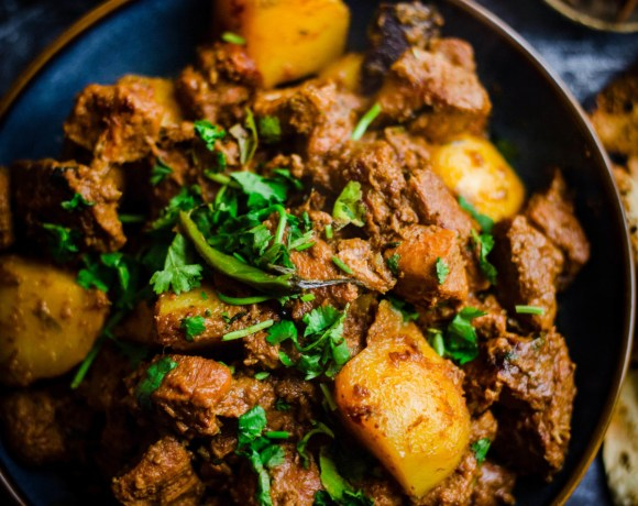 Lamb and Potatoes in a bowl with roti at the side