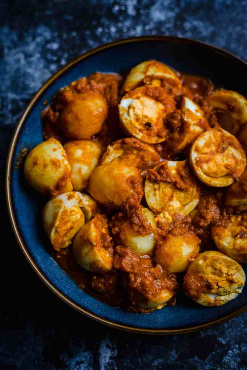 Egg and Potatoes in a red sauce in blue bowl on a blue backdrop