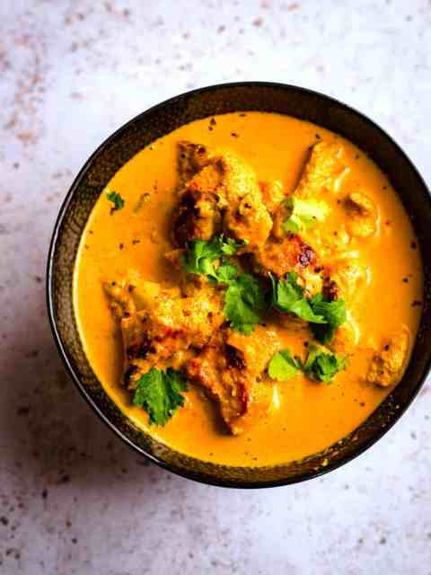 Butter Chicken in a bowl with Coriander as garnish