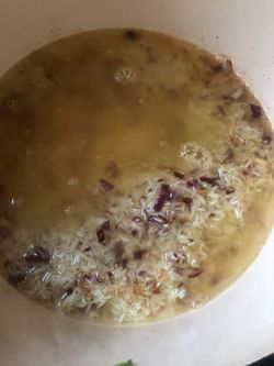 Rice, stock and onions added to pot