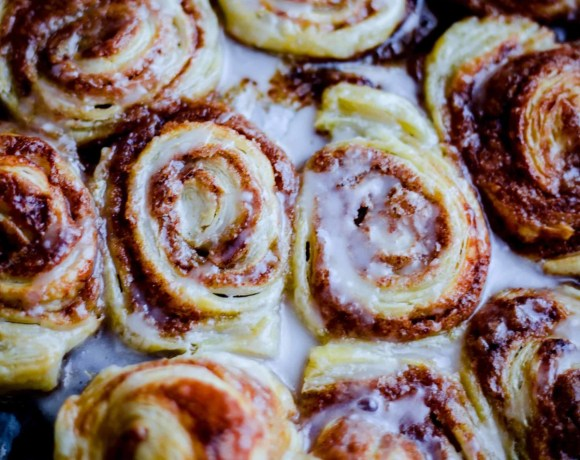 Puff Pastry Cinnamon Rolls on a tray, topped with icing