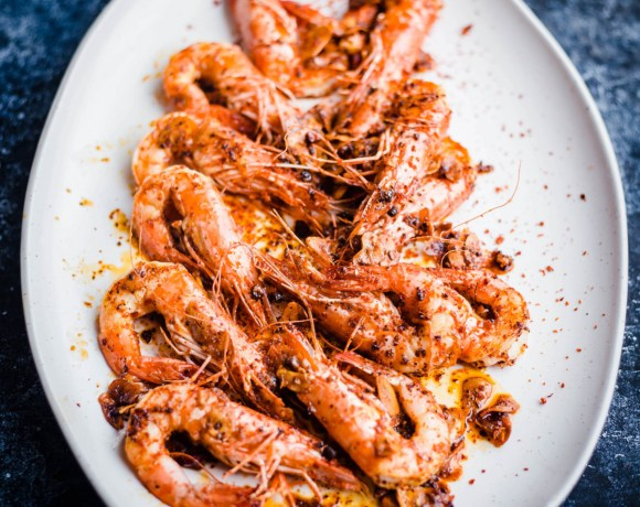 A pile of Chilli Garlic Prawns in a white oval plate