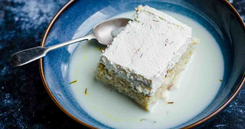Saffron Milk Cake in a blue bowl with a spoon