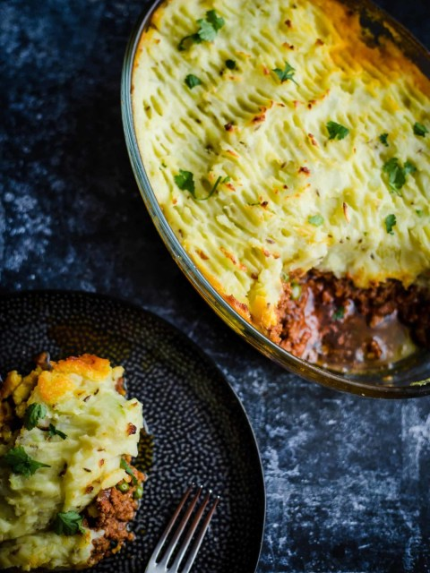 Indian Shepherd's Pie in a casserole dish with a portion in a plate at the side