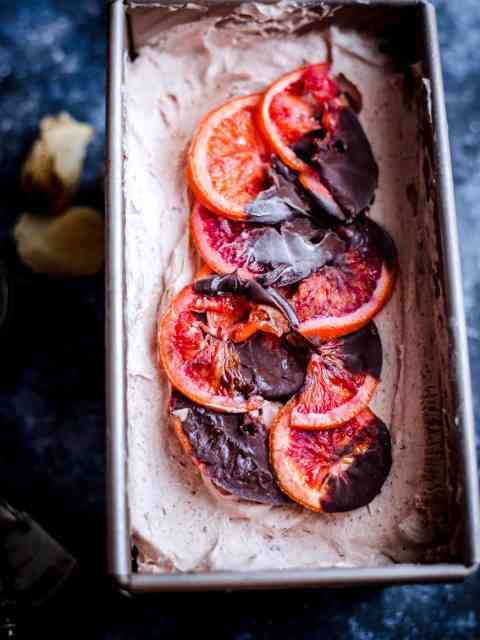 Blood Orange Ice Cream in a tin with chocolate orange slices on top