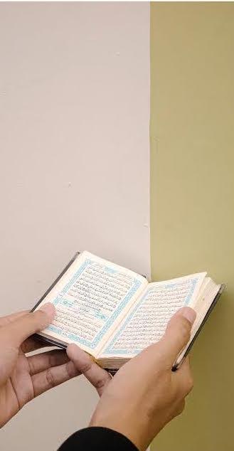 Hands holding open Quran