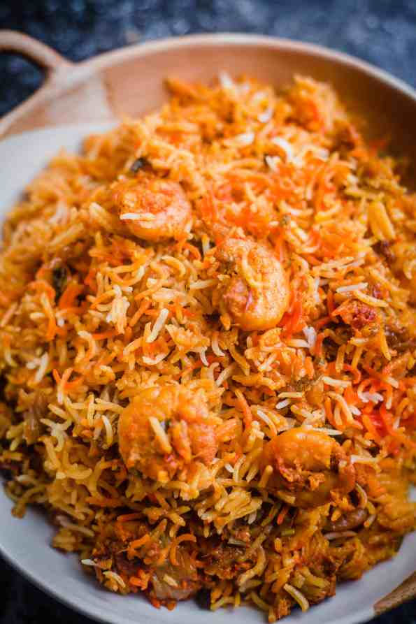 Prawn Biryani in a white and terracotta dish with handles on a table