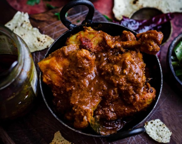 Chicken Bhuna in small wok with papadums scattered around