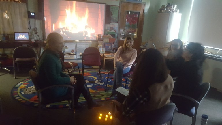 A group of women sit chatting in a circle of chairs in a darkened classroom. Behind them, a video of a roaring fireplace is projected onto a whiteboard from a laptop.