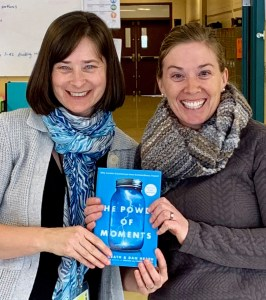 Host Jeanie Phillips, left and guest Rachel Mark, right hold a copy of the book The Power of Moments