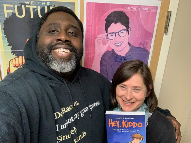 Guest Mike Hill, left, and host Jeanie Phillips, right, with the book Hey, Kiddo.