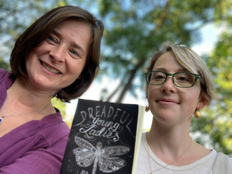 Jeanie Philips (l) and Sarah Birgé, with a copy of Dreadful Young Ladies and Other Stories, by Kelly Barnhill