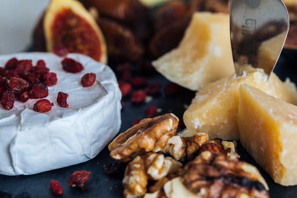 Tisch-Deko zu Erntedank: Detailfotografie von Walnüssen, Käse und Feigen auf Schieferplatte