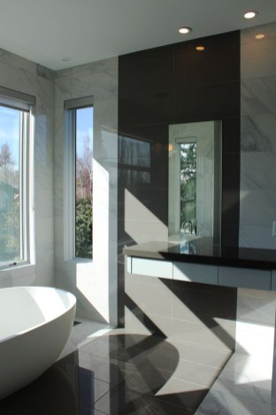 Bianco Carrara imitation porcelain installed in a bathroom along with Segment Charcoal porcelain tile