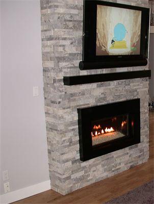 Silver Cubic Random Strip Ledgestone installed on a fireplace