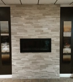 Wooden White Cubic Random Strip Ledgestone installed on a fireplace in a showroom