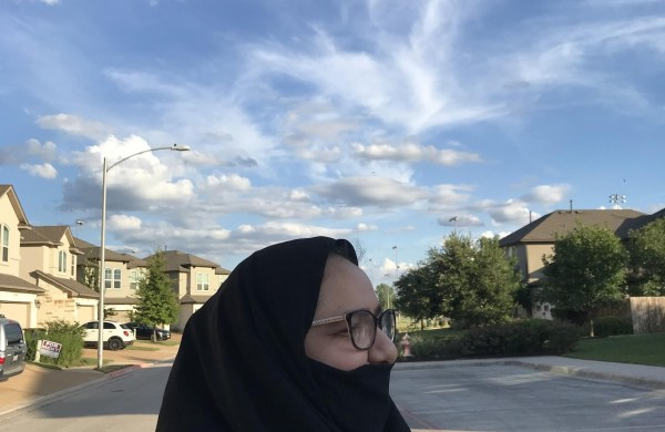 A woman with a veil standing on a street in the US