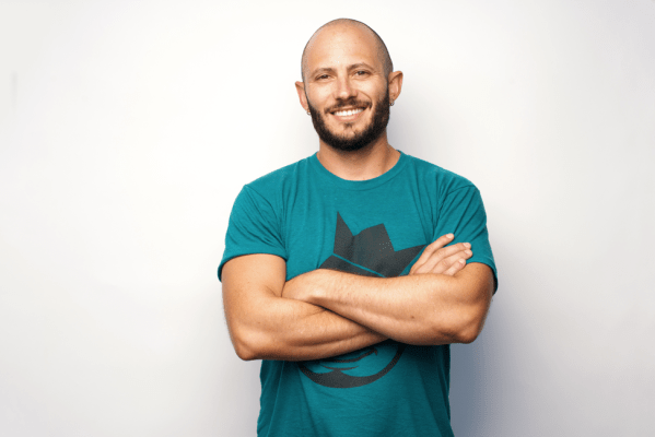Noah Kagen in a green t-shirt, with folded arms and smiling.