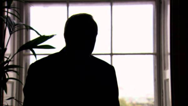 identity-protecting silhouette of Nick Szabo before a window, backlit