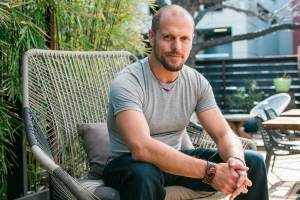 Tim Ferriss in jeans and a t-shirt sitting forward on a patio chair.