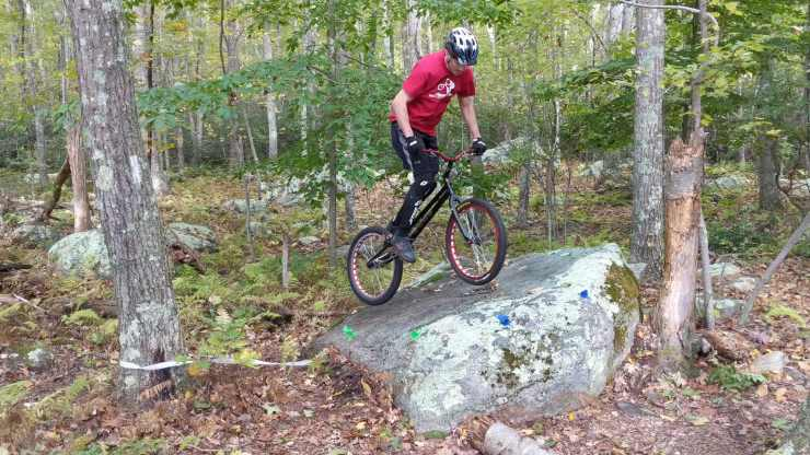 Trials biking competition - riding on a boulder