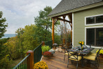 Exterior, horizontal, rear deck with table setting and sitting area looking out to Cayuga Lake