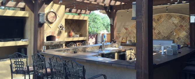 Hardscaping in backyard with outdoor kitchen and pergola