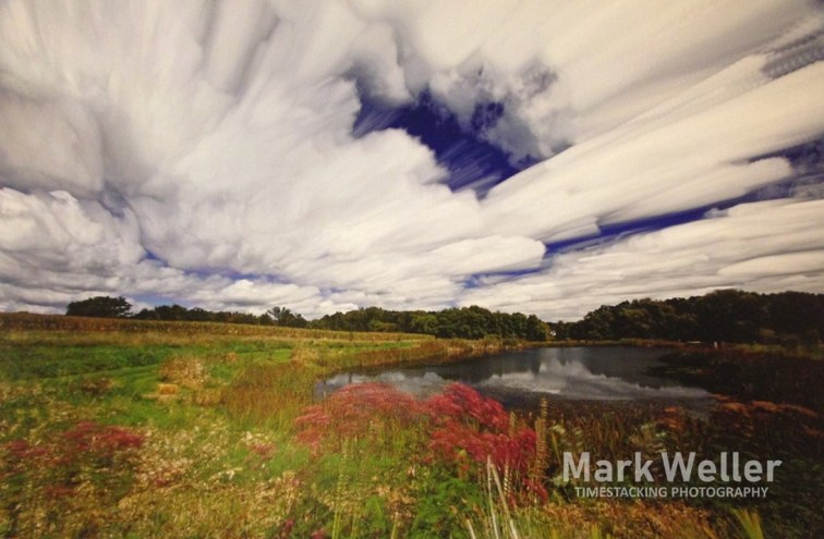 Timestack photography of clouds over river and field