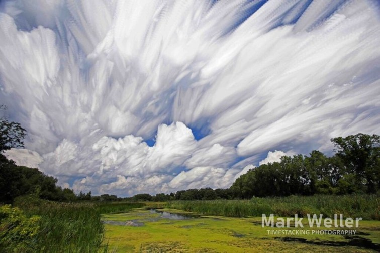 Timestack photography of clouds over water trees