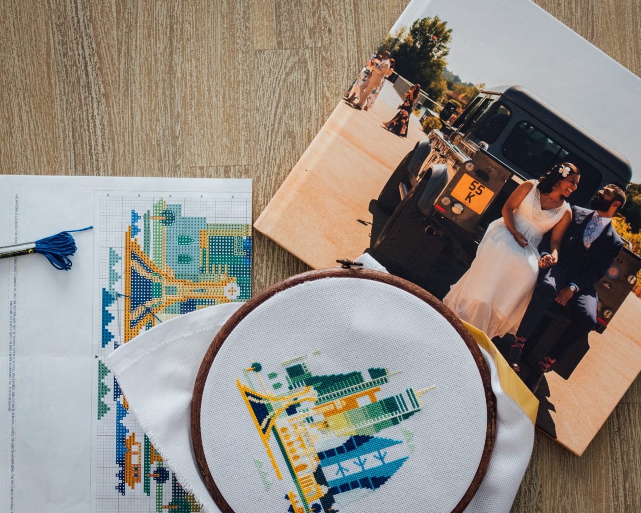 Photo of a wedding album and cross-stitch pattern on a coffee table.