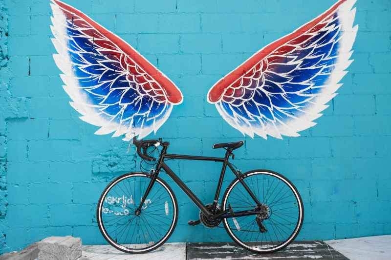 black road bike leaning on red blue and white wing graffiti wall
